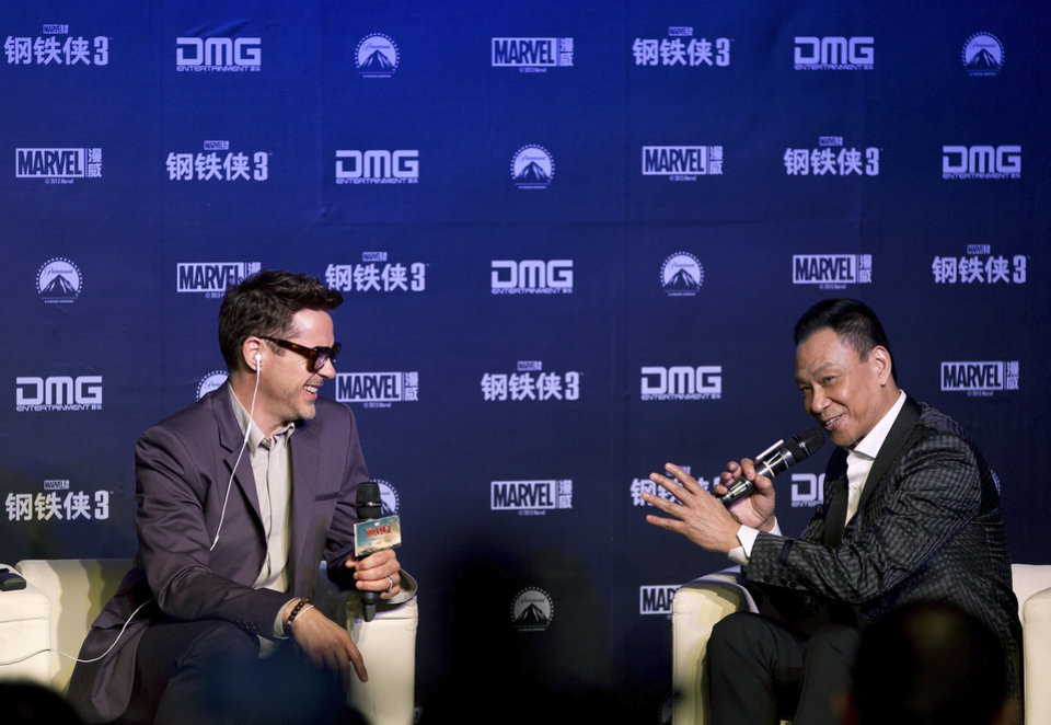 Photo - U.S. actor Robert Downey Jr., left, shares a light moment with Chinese actor Wang Xueqi on stage during a world premiere event of his new movie