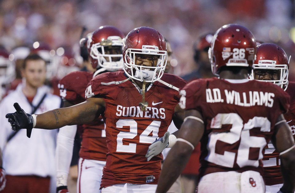 Photo -  Oklahoma running back Brennan Clay (24) greets teammate Damien Williams (26) on the sidelines after Williams scored a touchdown against Texas Tech in the fourth quarter of an NCAA college football game in Norman, Okla., Saturday, Oct. 26, 2013. Oklahoma won 38-30. (AP Photo/Sue Ogrocki)