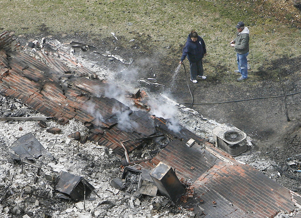 Photo - A couple waters down the ashes of their home near Choctaw High School in Choctaw, OK, Friday, April 10, 2009 after a wildfire destroyed their home and dozens of others. Photo by Paul Hellstern