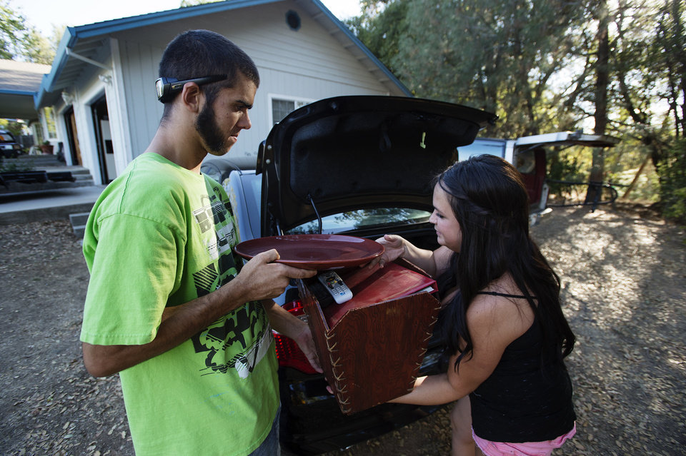Kayla Stanton, right, and Preston Holley, left, pack up belongings for friends as the Rim Fire threatens the small town of Tuolumne, Calif., Friday, Aug. 23, 2013. The giant wildfire raging out of control grew to nearly 200 square miles Friday and spread into Yosemite National Park.  (AP Photo/The Modesto Bee, Andy Alfaro) LOCAL TV OUT (KXTV10, KCRA3, KOVR13, FOX40, KMAX31, KQCA58, CENTRAL VALLEY TV); LOCAL PRINT OUT (TURLOCK JOURNAL, CERES COURIER, OAKDALE LEADER, MODESTO VIEW, PATTERSON IRRIGATOR, MANTECA BULLETIN, RIPON, RECROD, SONORA UNION DEMOCRAT, AMADOR LEDGER DISPATCH, ESCALON TIMES, CALAVERAS ENTERPRISE, RIVERBANKS NEWS) LOCAL INTERNET OUT (TURLOCK CITY NEWS.COM, MOTHER LODE.COM)