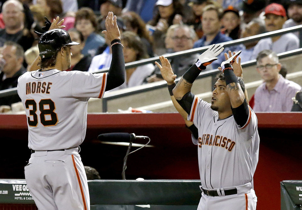 Photo - San Francisco Giants' Michael Morse (38) celebrates his RBI double with Hector Sanchez, right, during the sixth inning of a baseball game against the Arizona Diamondbacks, Wednesday, April 2, 2014, in Phoenix. (AP Photo/Ross D. Franklin)