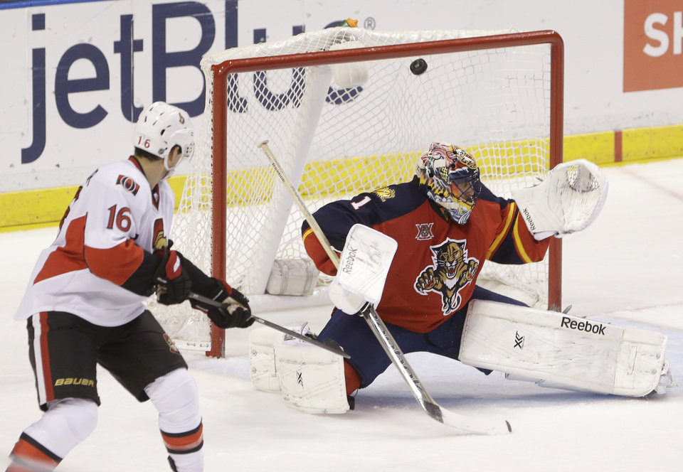 Photo - Ottawa Senators left wing Clarke MacArthur (16) scores a goal against Florida Panthers goalie Roberto Luongo (1) during the second period of an NHL hockey game, Tuesday, March 25, 2014 in Sunrise, Fla. (AP Photo/Wilfredo Lee)