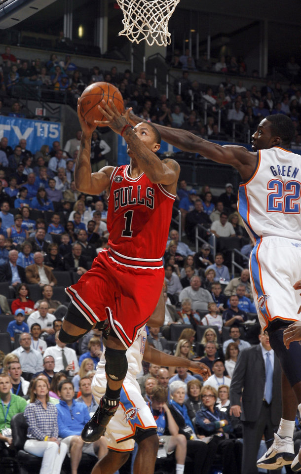 Photo - Chicago's Derrick Rose shoots as Oklahoma City's Jeff Green defends during the NBA season opener basketball game between the Oklahoma City Thunder and the Chicago Bulls in the Oklahoma City Arena on Wednesday, Oct. 27, 2010. Photo by Sarah Phipps, The Oklahoman
