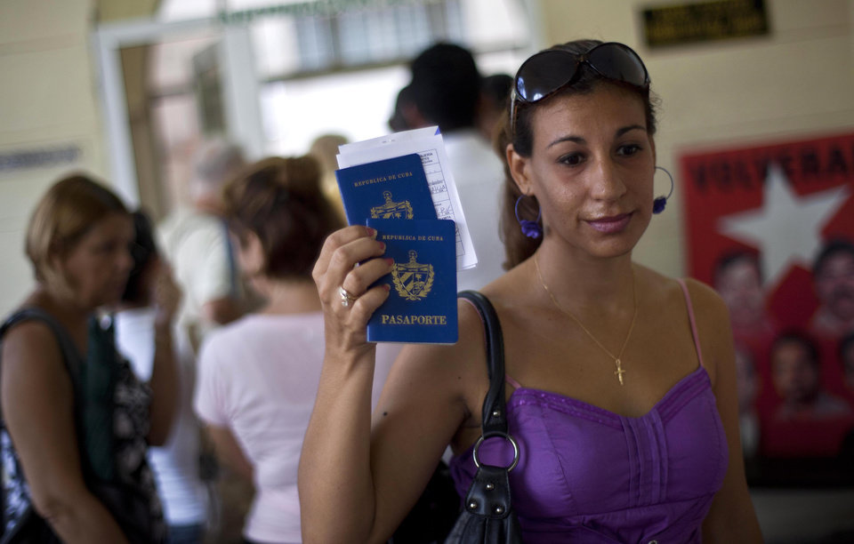Photo -   A woman shows her passport and that of her son to reporters as she leaves an immigration office in Havana, Cuba, Tuesday, Oct 16, 2012. The Cuban government announced Tuesday that it will no longer require islanders to apply for an exit visa, eliminating a much-loathed bureaucratic procedure that has been a major impediment for many seeking to travel overseas for more than a half-century. (AP Photo/Ramon Espinosa)