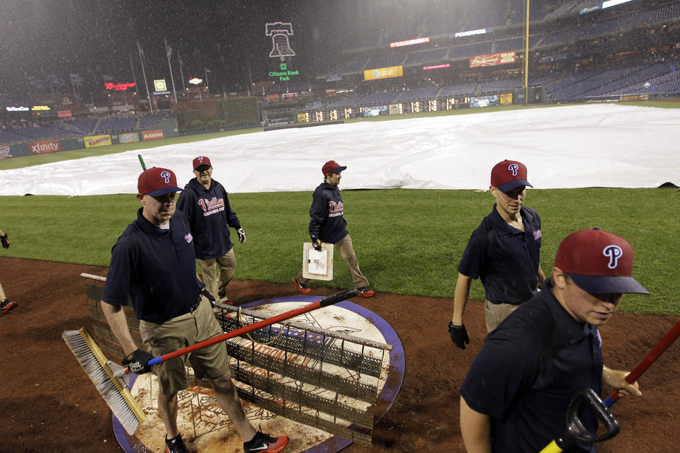 Photo - Grounds crew members cover the field during a rain delay in the sixth inning of a baseball game between the Philadelphia Phillies and the Washington Nationals, Saturday, May 3, 2014, in Philadelphia. (AP Photo/Laurence Kesterson)