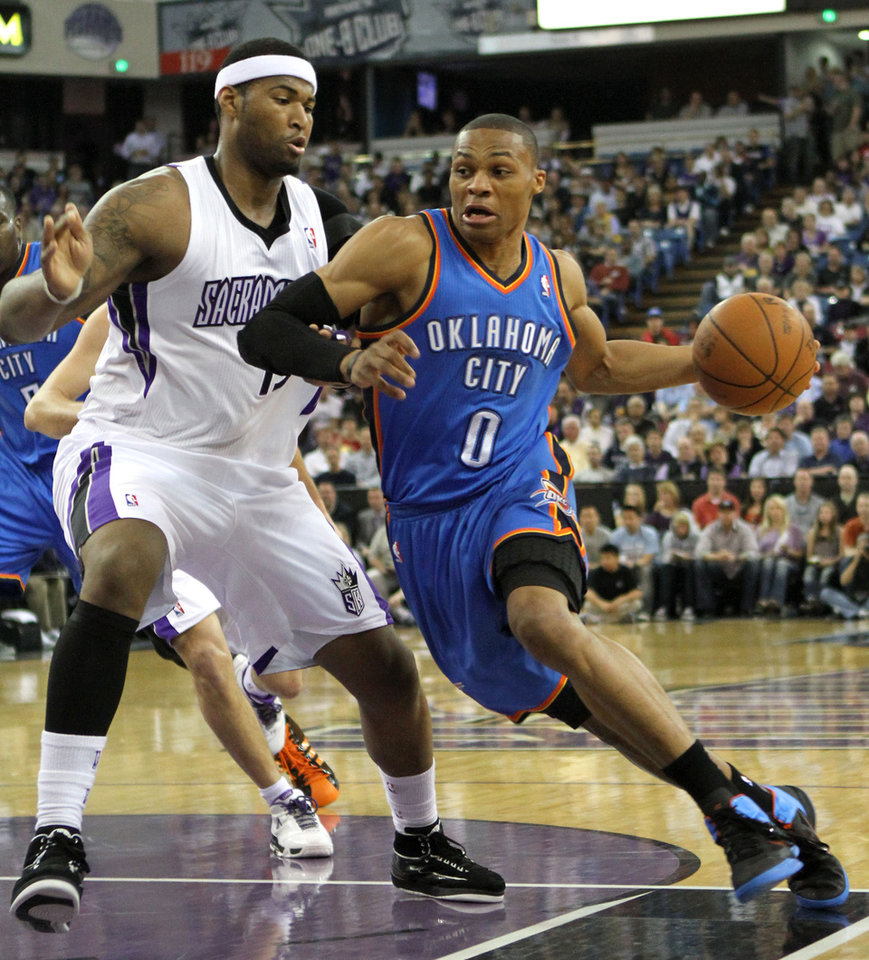 Oklahoma City Thunder guard Russell Westbrook, right, drives to the basket against Sacramento Kings center DeMarcus Cousins during the first quarter of an NBA basketball game in Sacramento, Calif., Monday, April 11, 2011. (AP Photo/Rich Pedroncelli) ORG XMIT: SCA103