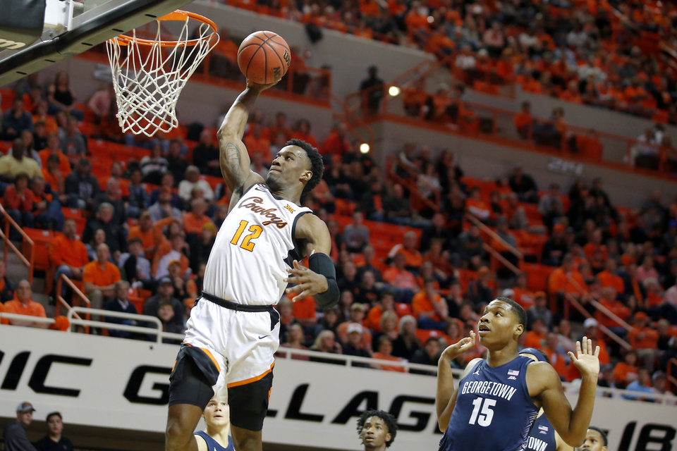 Photo - Oklahoma State's Cameron McGriff (12) dunks the ball in front of Georgetown's Myron Gardner (15) during a college basketball game between the Oklahoma State University Cowboys (OSU) and the Georgetown Hoyas at Gallagher-Iba Arena in Stillwater, Okla., Wednesday, Dec. 4, 2019. Georgetown won 84-71. [Bryan Terry/The Oklahoman]