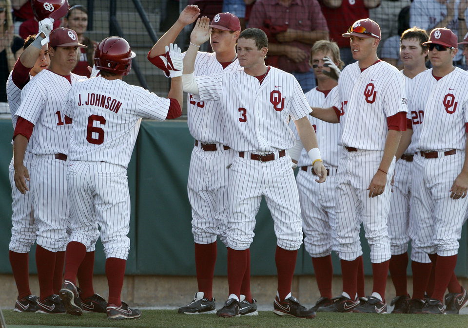 Photo - Jamie Johnson is greeted after his game opening home run as the University of Oklahoma plays Wichita State at L. Dale Mitchell Park in the NCAA Regional baseball tournament in Norman, Okla. on Friday, May 29, 2009. 