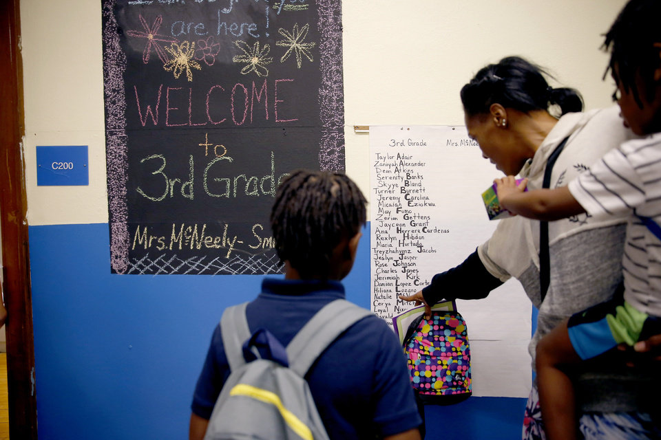 Photo - Loria Phillips helps her son Jhaidon, 8, look for his third grade classroom as she carries her other son Adrian Phillips, 3, inside Britton Elementary on the first day of school in Oklahoma City, Monday, Aug. 12, 2019. [Bryan Terry/The Oklahoman]