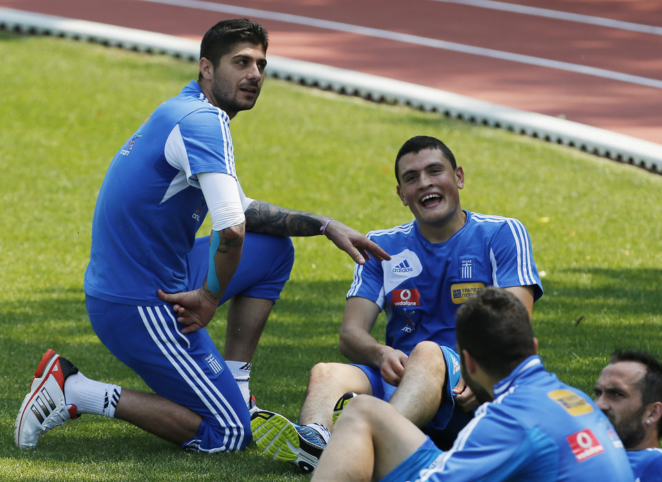 Greece's Kyriakos Papadopoulos, right, and goalkeeper Michalis Sifakis joke each other during a training session at the Euro 2012 soccer championship in Legionowo about 25 kilometers (15 miles) north of Warsaw, Poland on Monday, June 18, 2012. (AP Photo/Thanassis Stavrakis)