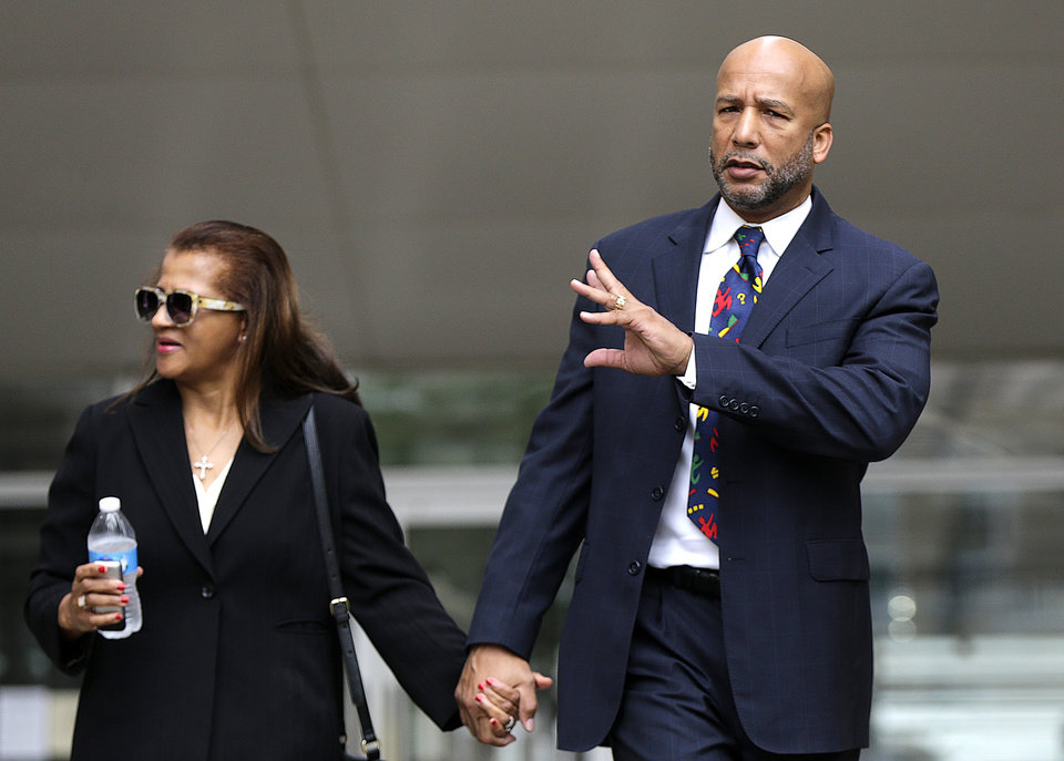 Photo - Former New Orleans Mayor Ray Nagin leaves federal court with his wife, Seletha Nagin, after being sentenced in New Orleans, Wednesday, July 9, 2014. Nagin was sentenced to 10 years in prison for bribery, money laundering and other corruption that spanned his two terms as mayor, including the chaotic years after Hurricane Katrina hit in 2005. (AP Photo/Gerald Herbert)