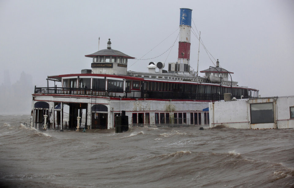 An historic ferry boat named the Binghamton is swamped by the waves of the Hudson River in Edgewater, N.J., Monday, Oct. 29, 2012, as Hurricane Sandy lashes the East Coast. Hurricane Sandy continued on its path Monday, as the storm forced the shutdown of mass transit, schools and financial markets, sending coastal residents fleeing, and threatening a dangerous mix of high winds and soaking rain.  (AP Photo/Craig Ruttle) ORG XMIT: NJCR110