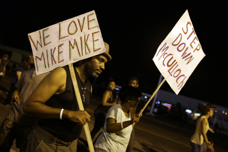 Photo - Protesters march Thursday, Aug. 21, 2014, in Ferguson, Mo. Protesters again gathered Thursday evening, walking in laps near the spot where Michael Brown was shot. Some were in organized groups, such as clergy members. More signs reflected calls by protesters to remove the prosecutor, Robert McCulloch, from the case. (AP Photo/Jeff Roberson)