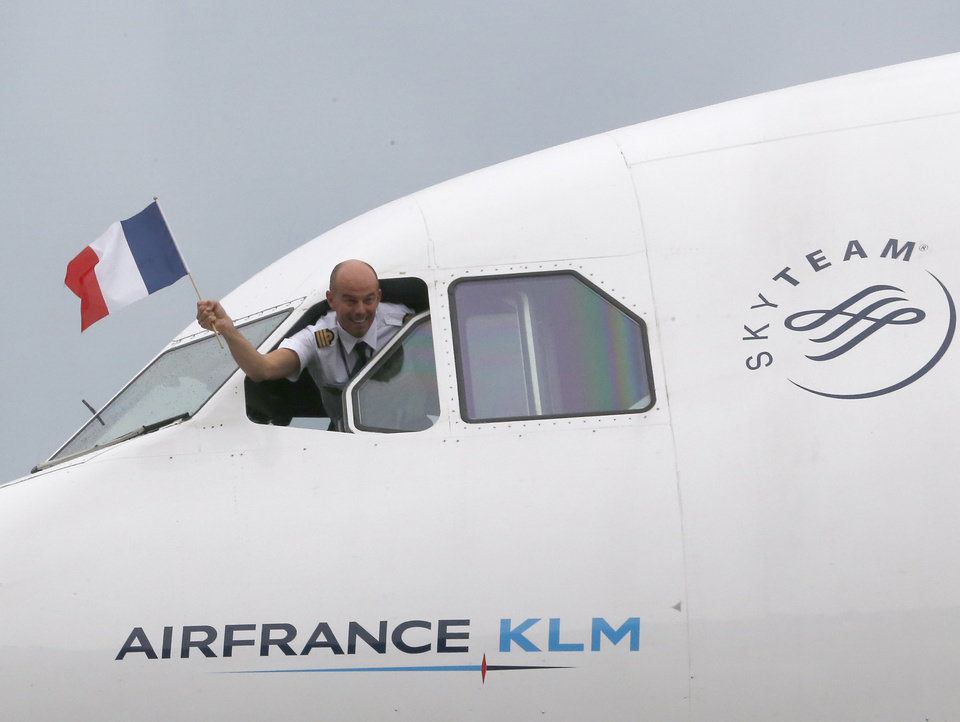 Photo - French pilot, Jose Cravinho, waves a French flag from the cockpit of the aircraft being used to fly the French World Cup team to Brazil at Lille -Lesquin  Airport as they prepare to travel to Brazil for the World Cup soccer tournament, in Lesquin northern France, Monday, June 9, 2014. France is part of Group E  that includes  Ecuador, Switzerland and Honduras, and will play Honduras in Porto Alegre in its opening match on June 15. (AP Photo/Jacques Brinon)