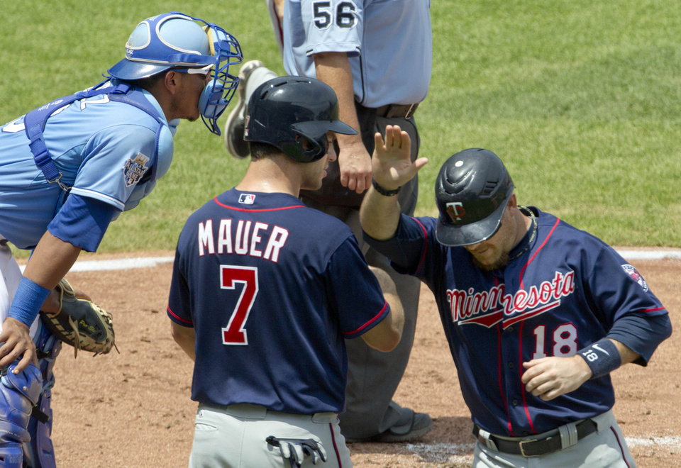 Photo -   Minnesota Twins' Joe Mauer (7) and Ryan Doumit (18) congratulate each other after scoring past Kansas City Royals catcher Salvador Perez, left, during the third inning of a baseball game at Kauffman Stadium in Kansas City, Mo., Sunday, July 22, 2012. The pair scored on a double by Brian Dozier. (AP Photo/Orlin Wagner)