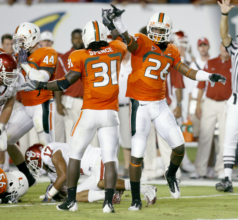 Photo - CELEBRATION: Miami's Sean Spence, left, and Ray Ray Armstrong celebrate as Mossis Madu of OU gets up during the college football game between the University of Oklahoma (OU) Sooners and the University of Miami (UM) Hurricanes at Land Shark Stadium in Miami Gardens, Florida, Saturday, October 3, 2009. Photo by Bryan Terry, The Oklahoman ORG XMIT: KOD