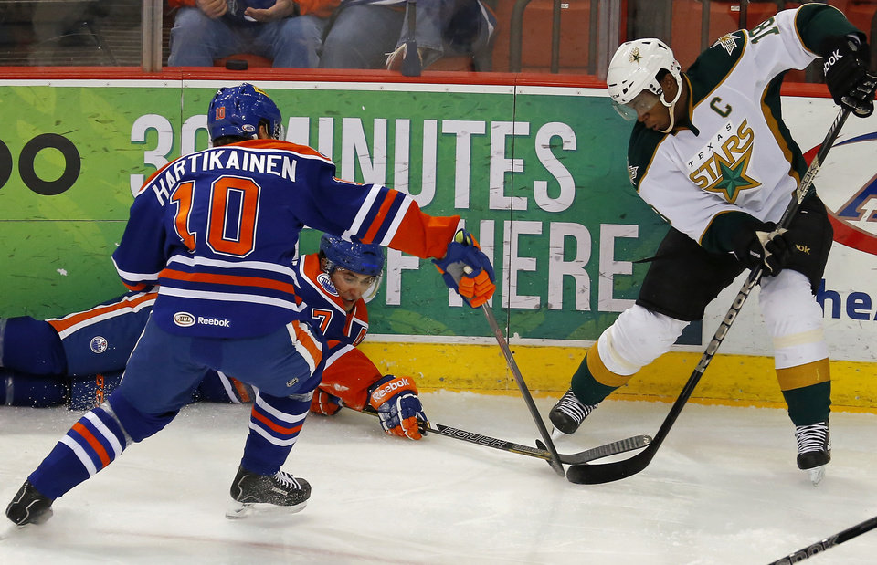 Photo - Teemu Hartikainen, left, and Jordan Eberle of the Oklahoma City Barons go for the puck beside Josh Green of the Texas Stars during an AHL hockey game at the Cox Convention in Oklahoma City, Friday, Dec. 21, 2012. Photo by Bryan Terry, The Oklahoman