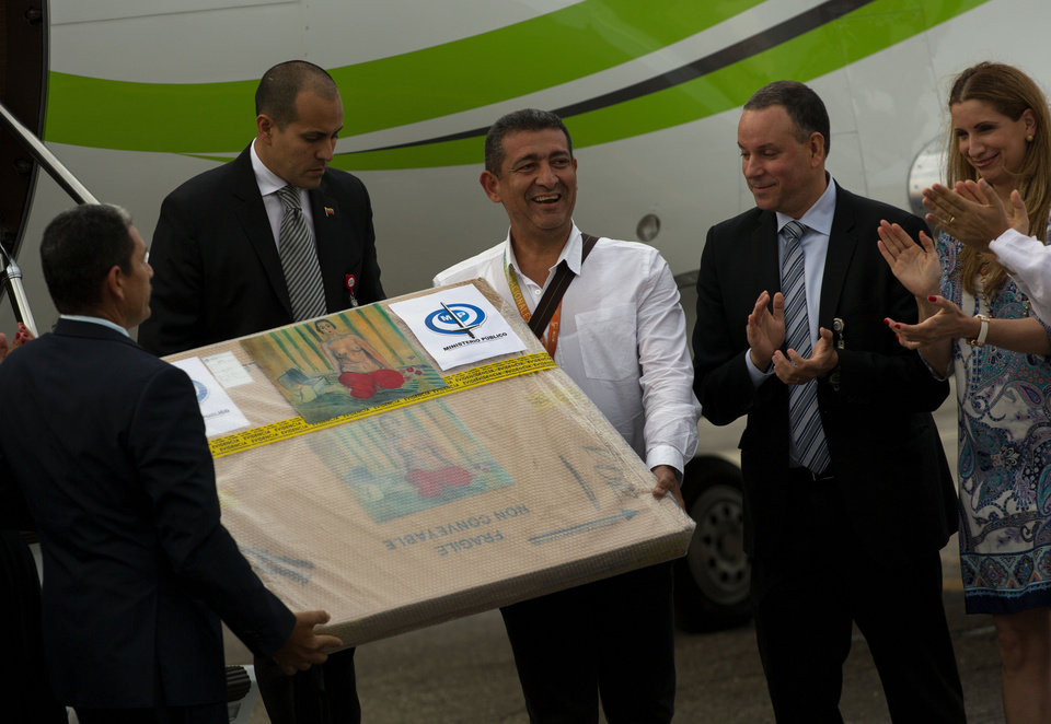 Photo - Venezuelan government handlers hold a package containing the painting