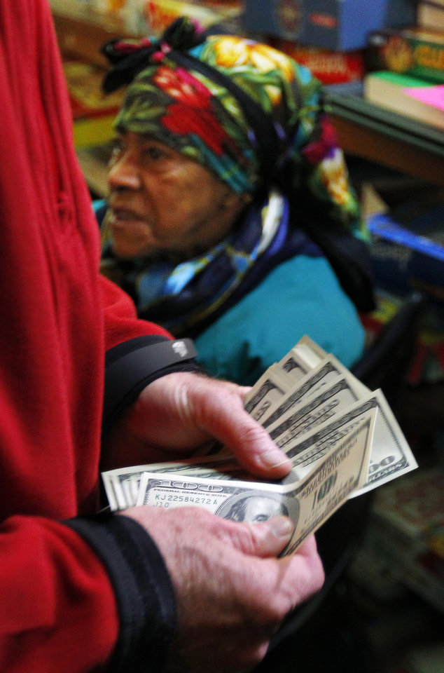 Photo - A wealthy philanthropist from Kansas City, Mo., known as Secret Santa, distributes $100 dollar bills to needy people at St. Joseph's Social Service Center in Elizabeth, N.J., Thursday, Nov. 29, 2012. (AP Photo/Rich Schultz)