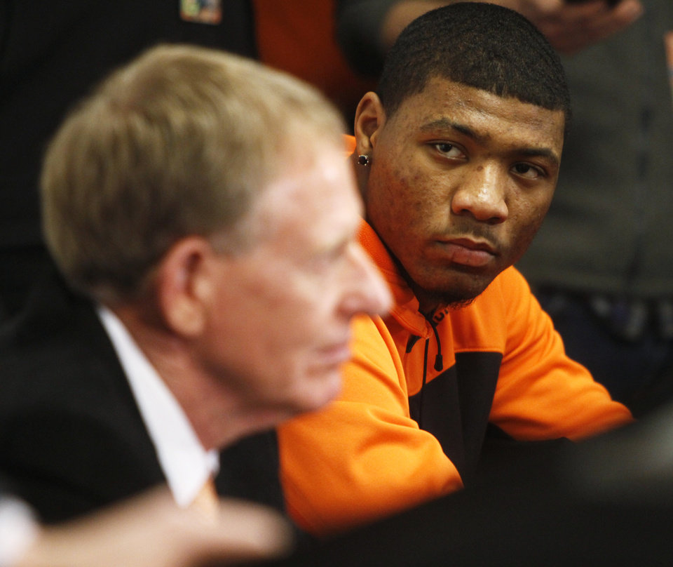 Photo - Oklahoma State basketball player Marcus Smart (right) and Oklahoma State athletic director Mike Holder look on as a press conference is held in Gallagher Iba Arena on Sunday, Feb. 9, 2014. The press conference was held the day after star player Marcus Smart shoved a fan during an altercation in a game Saturday, Feb. 8, 2014. Smart was given a three game suspension by the Big 12 conference and Oklahoma State. Photo by KT King/The Oklahoman