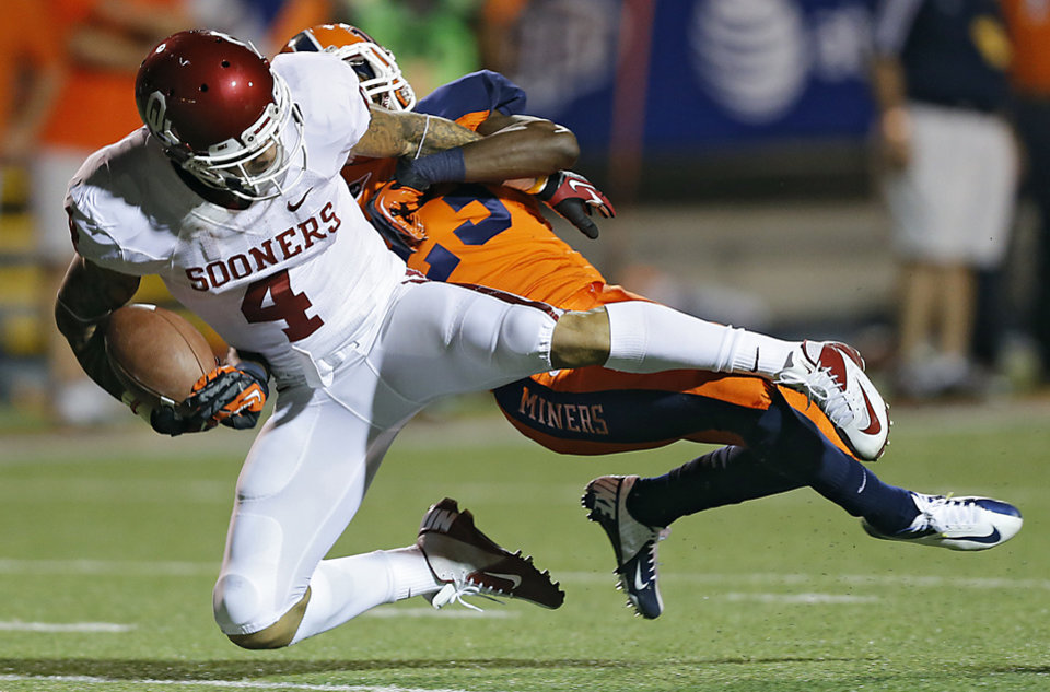 Photo - Oklahoma Sooners wide receiver Kenny Stills (4) is brought down by UTEP's Terr'l Mark (23) during the college football game between the University of Oklahoma Sooners (OU) and the University of Texas El Paso Miners (UTEP) at Sun Bowl Stadium on Saturday, Sept. 1, 2012, in El Paso, Tex.  Photo by Chris Landsberger, The Oklahoman
