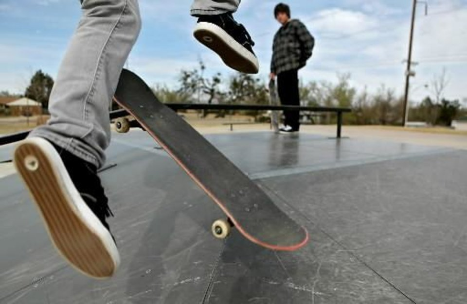 Photo - Ryan Bell, of Midwest City, watches Matt Collins, of Choctaw, attempt a trick on the hip as they skate at Lions Skate Park in Midwest City on Wednesday, March 11, 2008. By John Clanton