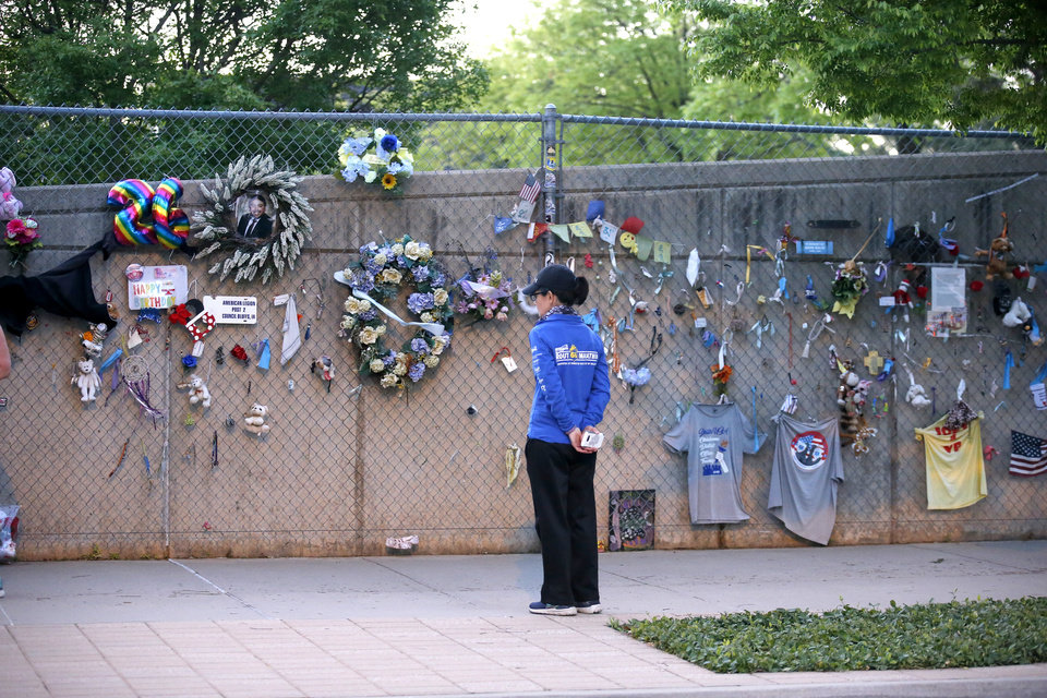 Photo - A person pauses for 168 seconds of silence before runners ran the route of the Oklahoma City Memorial Marathon in Oklahoma City,  Sunday, April 26, 2020.  The 20th Oklahoma City Memorial Marathon was delayed until October because of Covid-19. [Sarah Phipps/The Oklahoman]