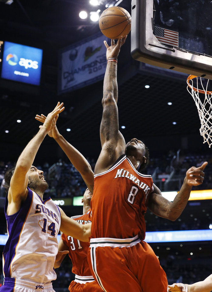 Milwaukee Bucks' Larry Sanders (8) blocks the shot of Phoenix Suns' Luis Scola (14), of Argentina, in the second half during an NBA basketball game on Thursday, Jan. 17, 2013, in Phoenix. The Bucks defeated the Suns 98-94. (AP Photo/Ross D. Franklin)