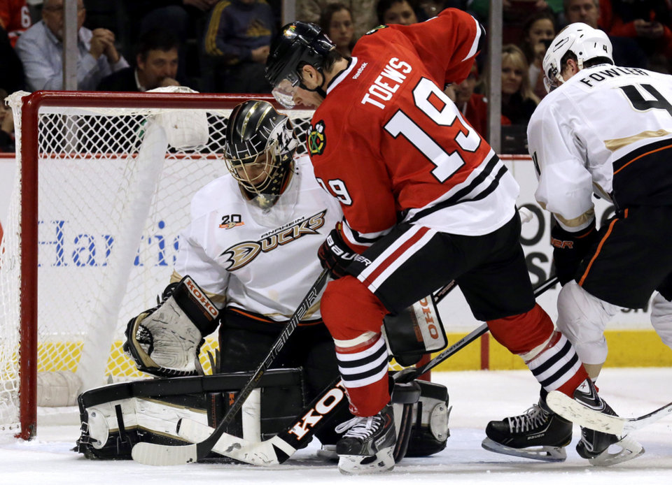 Photo - Chicago Blackhawks' Jonathan Toews (19) shoots against Anaheim Ducks goalie Jonas Hiller (10) during the second period of an NHL hockey game in Chicago, Friday, Jan. 17, 2014. (AP Photo/Nam Y. Huh)