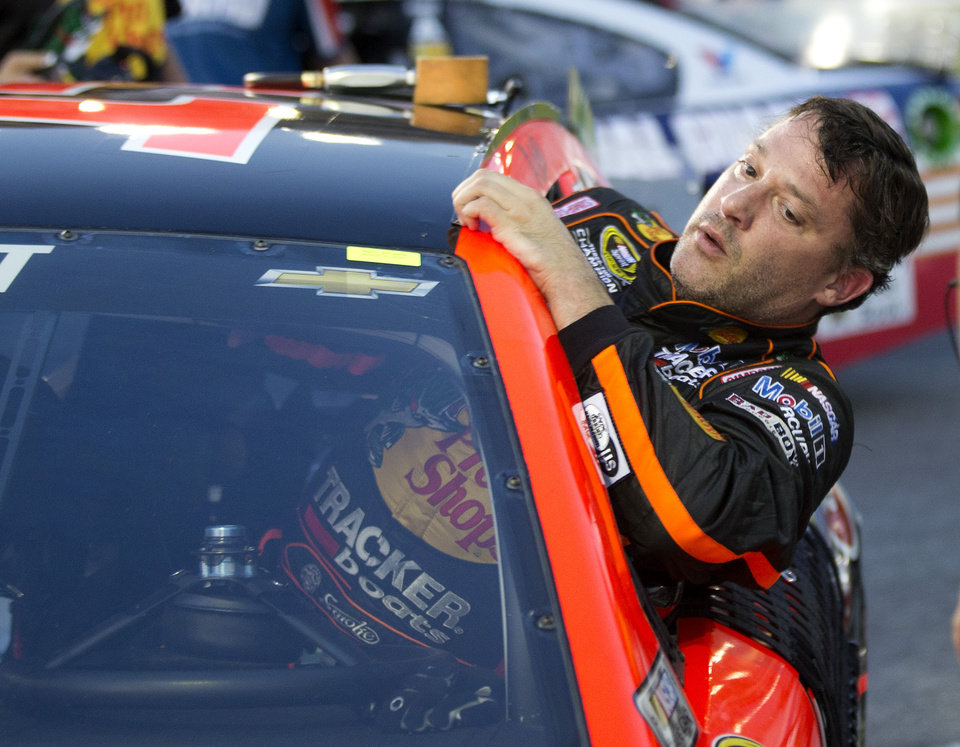 Photo - Sprint Cup Series driver Tony Stewart (14) climbs out of his car after qualifying for Sunday's Oral B USA 500 NASCAR auto race at Atlanta Motor Speedway Friday, Aug. 29, 2014, in Hampton, Ga. (AP Photo/John Bazemore)