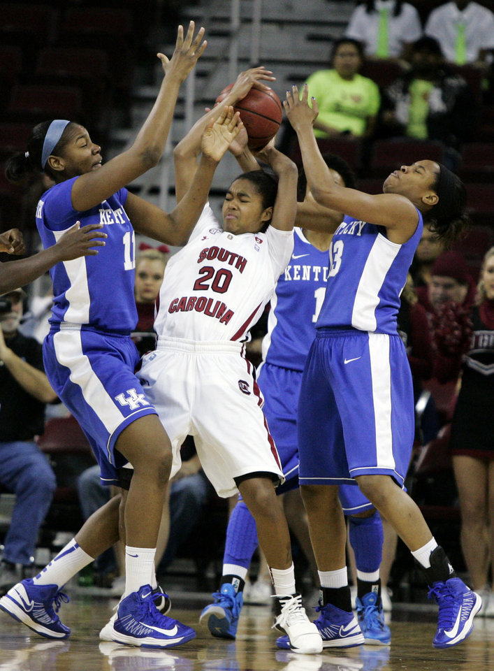 Photo - Kentucky's DeNesha Stallworth (11) and Bria Goss (13) force a turnover from South Carolina's Sancheon White (20) during the first half of their NCAA college basketball game, Thursday, Jan. 24, 2013, in Columbia, S.C. (AP Photo/Mary Ann Chastain)