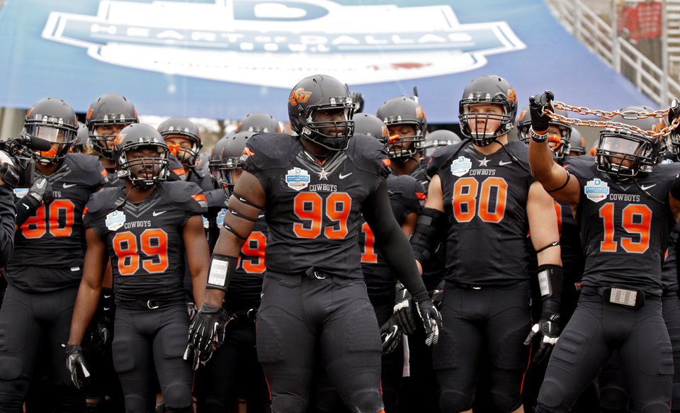 Photo - The Oklahoma State team gets ready to take the field before the Heart of Dallas Bowl football game between Oklahoma State University and Purdue University at the Cotton Bowl in Dallas, Tuesday, Jan. 1, 2013. Oklahoma State won 58-14. Photo by Bryan Terry, The Oklahoman