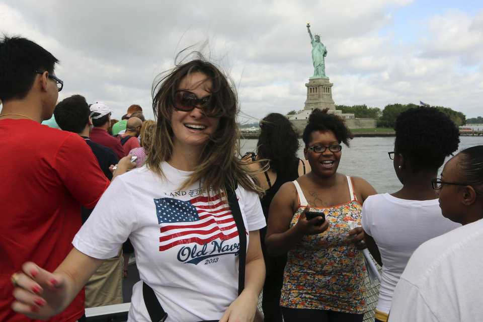 Photo - Visitors to fhe Statue of Liberty take photos as they arrive on the first tourist ferry to leave Manhattan, Thursday, July 4, 2013, in New York. The Statue of Liberty finally reopened on the Fourth of July months after Superstorm Sandy swamped its island in New York Harbor as Americans across the country marked the holiday with fireworks and barbecues. (AP Photo/Mary Altaffer)