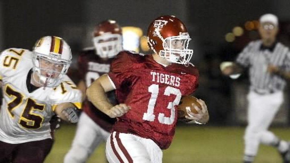 Tuttle quarterback Sterling Koons runs up the middle past Clinton defender (75) Jarrett Richert during 2nd qtr. in Class 3A matchup between Tuttle and Clinton at Bill Hinkle Field Friday night. By Jim Beckel