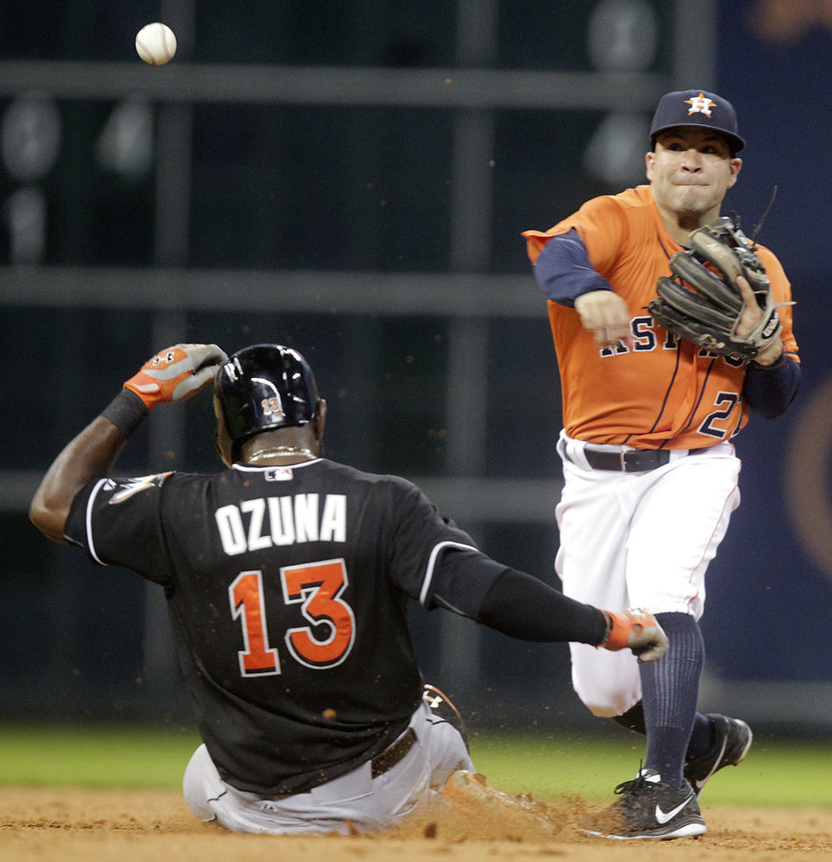 Photo - Houston Astros second baseman Jose Altuve throws to first after forcing out Miami Marlins' Marcell Ozuna (13), getting Jeff Mathis at first to complete a double play during the fifth inning of a baseball game, Friday, July 25, 2014, in Houston. (AP Photo/Patric Schneider)