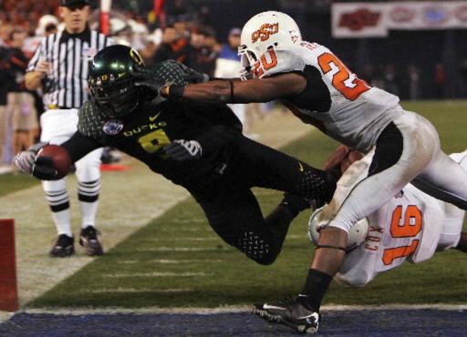 Photo - Oregon's LeGarrette Blount (9) dives into the end zone for a touchdown on a 29-yard run while Oklahoma State's Andre Sexton, right, and Perrish Cox (16) defend in the fourth quarter of the Holiday Bowl NCAA college football game in San Diego Tuesday, Dec. 30, 2008. Oregon won the game 42-31. AP Photo