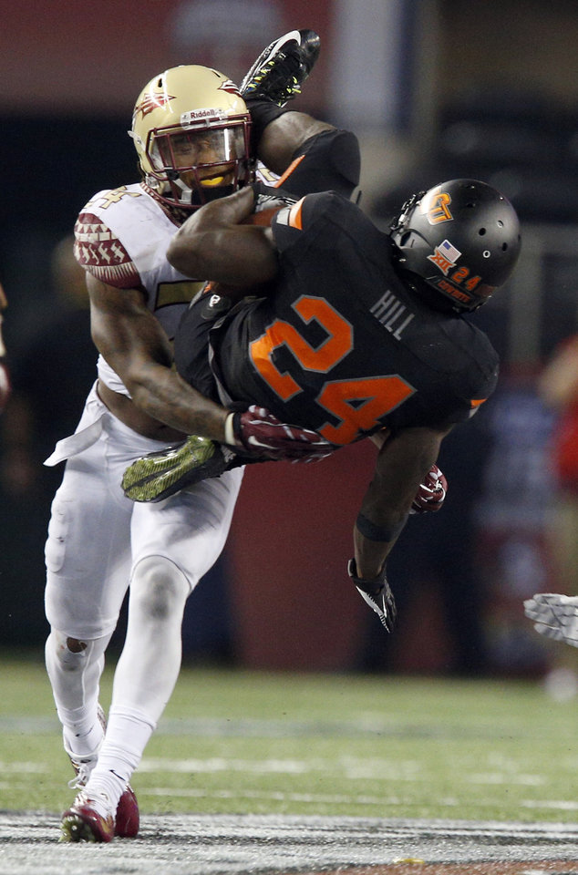 Photo - Florida State's Terrance Smith (24) tackles Oklahoma State's Tyreek Hill (24) during the college football game between Oklahoma State University (OSU) and Florida State University (FSU) at the AdvoCare Cowboys Classic at At&T Stadium in Arlington, Texas,  Saturday, Aug. 30, 2014. Photo by Sarah Phipps, The Oklahoman