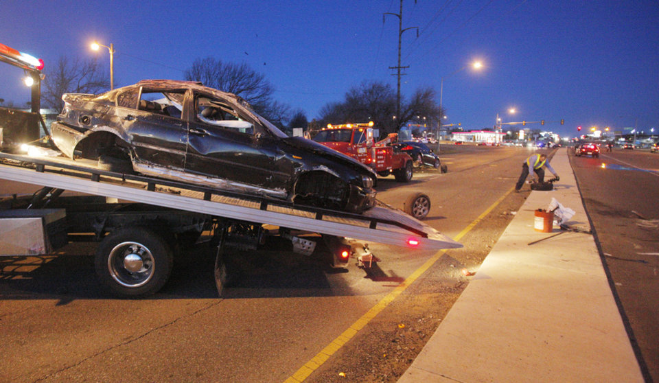 A BMW is loaded onto a wrecker as its tires are picked up by a wrecker driver in the background after an altercation between the occupants in two vehicles resulted in a fatality accident early Friday at Northwest Expressway and Wilshire Boulevard.  Photo by Paul B. Southerland, The Oklahoman