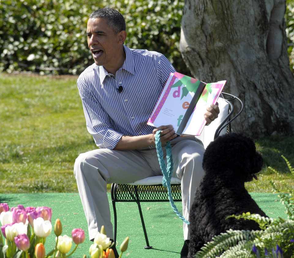 "President Barack Obama, accompanied by first  dog Bo, reads ""Chicka Chicka Boom Boom"" during the annual Easter Egg Roll on the South Lawn of the White House in Washington, Monday, April 1, 2013. (AP Photo/Susan Walsh)"