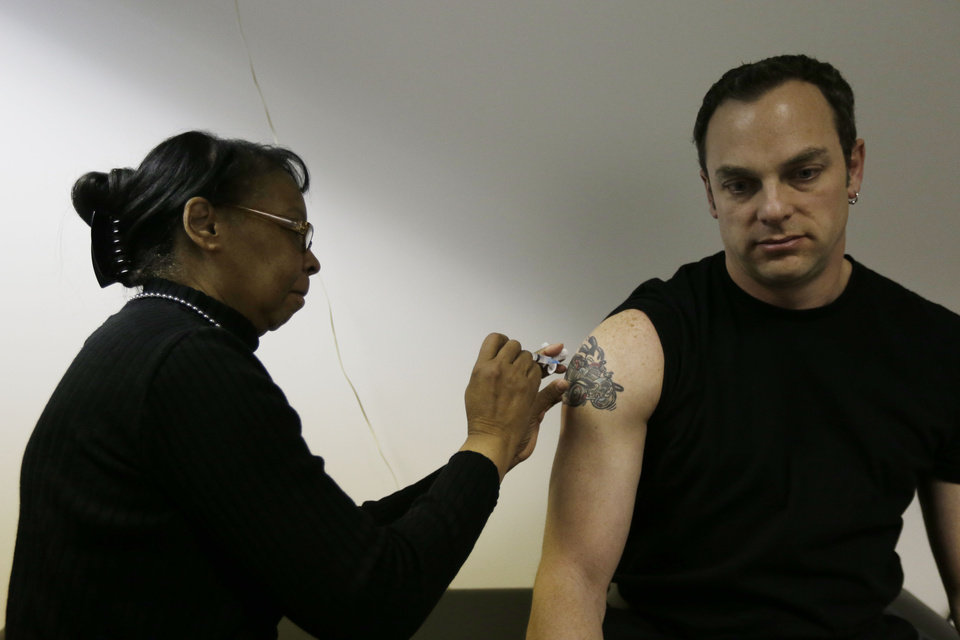 Pam Horn administers the flu vaccine to employee Michael Karolitzky at Philly Flu Shots on Thursday, Jan. 10, 2013, in Philadelphia. The flu season arrived early in the U.S. this year, but health officials and experts say it\'s too early to say this will be a bad one. Experts say evidence so far is pointing to a moderate flu season - it just looks worse because last year\'s season was so mild. Flu usually doesn\'t blanket the country until late January or February. Now, it\'s already widespread in more than 40 states. That could change when the next government report comes out Friday. (AP Photo/Matt Rourke)