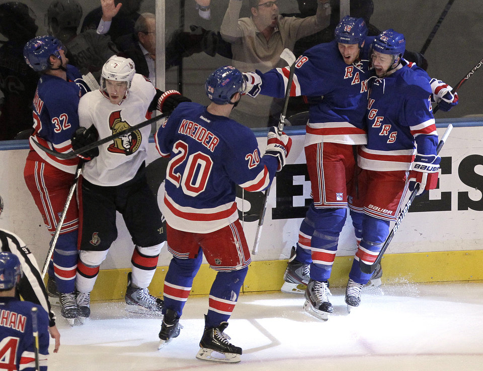 Photo -   Members of the New York Rangers celebrate a goal by Marc Staal, second from right, as Ottawa Senators' Kyle Turris, second from left, gets caught in the celebration during the second period of Game 7 of a first-round NHL hockey Stanley Cup playoff series on Thursday, April 26, 2012, in New York. (AP Photo/Julio Cortez)
