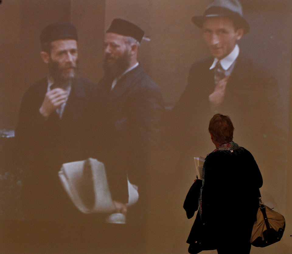 Photo - A visitor watches a color document movie of Nalewki Street in the Jewish district in pre-World War II Warsaw, at a new exhibition by the Museum of the History of Polish Jews, in Warsaw, Poland, on Thursday, March 27, 2014. The exhibition that will run through June 30 documents Jewish life in Warsaw before the Holocaust. (AP Photo/Czarek Sokolowski)