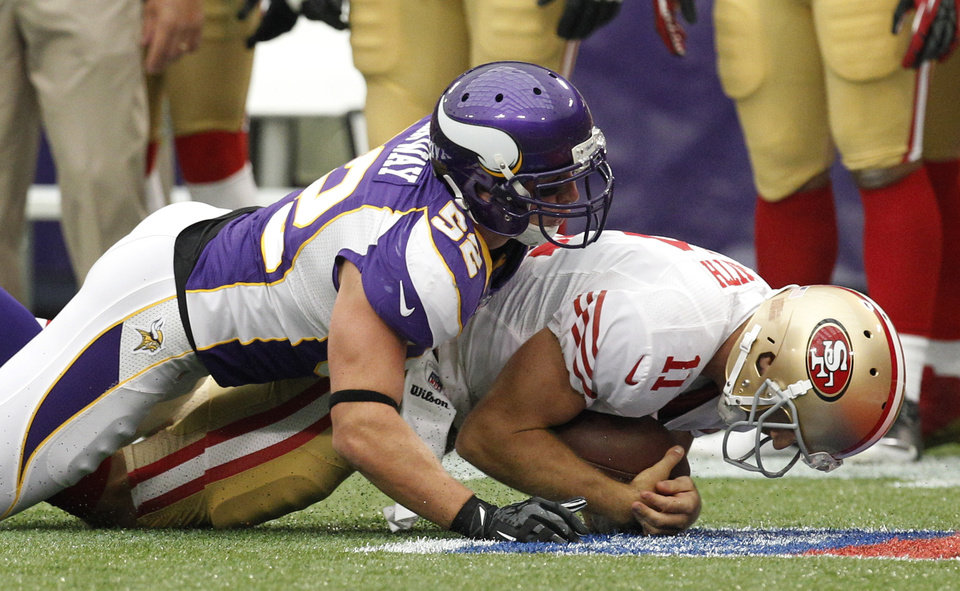 Photo -   Minnesota Vikings outside linebacker Chad Greenway, left, sacks San Francisco 49ers quarterback Alex Smith during the first half of an NFL football game on Sunday, Sept. 23, 2012, in Minneapolis. (AP Photo/Genevieve Ross)