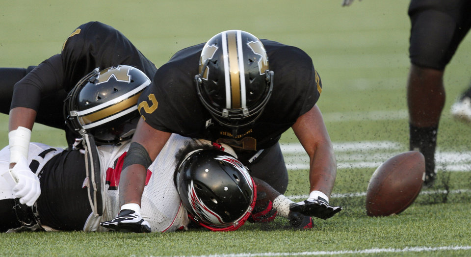 Photo - Midwest City's Ricky Reeves, left, and Myles Hogg force Del City's Adrian Fletcher to fumble during a high school football game in Midwest City, Okla., Friday, September 3, 2010.  Photo by Bryan Terry, The Oklahoman