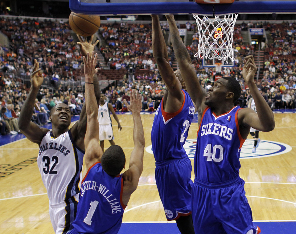 Photo - Memphis Grizzlies' Ed Davis (32) goes up for a shot against Philadelphia 76ers' Michael Carter-Williams (1), Thaddeus Young (21) and Jarvis Varnado (40) during the first half of an NBA basketball game, Saturday, March 15, 2014, in Philadelphia. (AP Photo/Matt Slocum)