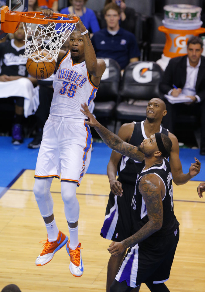Oklahoma City\'s Kevin Durant (35) dunks beside Sacramento\'s Travis Outlaw (25) and DeMarcus Cousins (15) during an NBA game between the Oklahoma City Thunder and the Sacramento Kings at Chesapeake Energy Arena in Oklahoma City, Friday, March 28, 2014. Oklahoma City on 94-81. Photo by Bryan Terry, The Oklahoman