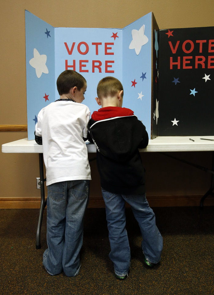 Greyson Caldwell, 6, left, and brother Zane, 5, mark their ballots at a children's election-day party Tuesday at the Moore Public Library.  PHOTOS BY STEVE SISNEY, THE OKLAHOMAN