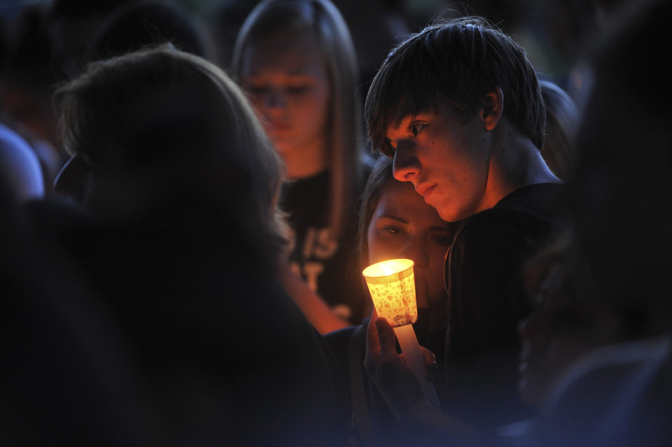 Photo - In this June 10, 2014 photo, people participate in a candlelight vigil for Emilio Hoffman, the victim of a shooting at Reynolds High School on Tuesday, in Troutdale, Ore. Authorities said a teen gunman armed with a rifle shot and killed the 14-year-old student and injured a teacher before he likely killed himself at the high school. (AP Photo/The Oregonian, Stephanie Yao Long)
