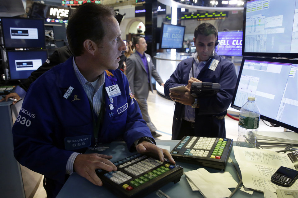 Photo - Specialist Glenn Carell, left, works at his post on the floor of the New York Stock Exchange, Thursday, July 3, 2014. The Dow Jones industrial average jumped above 17,000 for the first time Thursday after the government reported a surge in hiring last month that was much bigger than investors and economists were expecting. (AP Photo/Richard Drew)