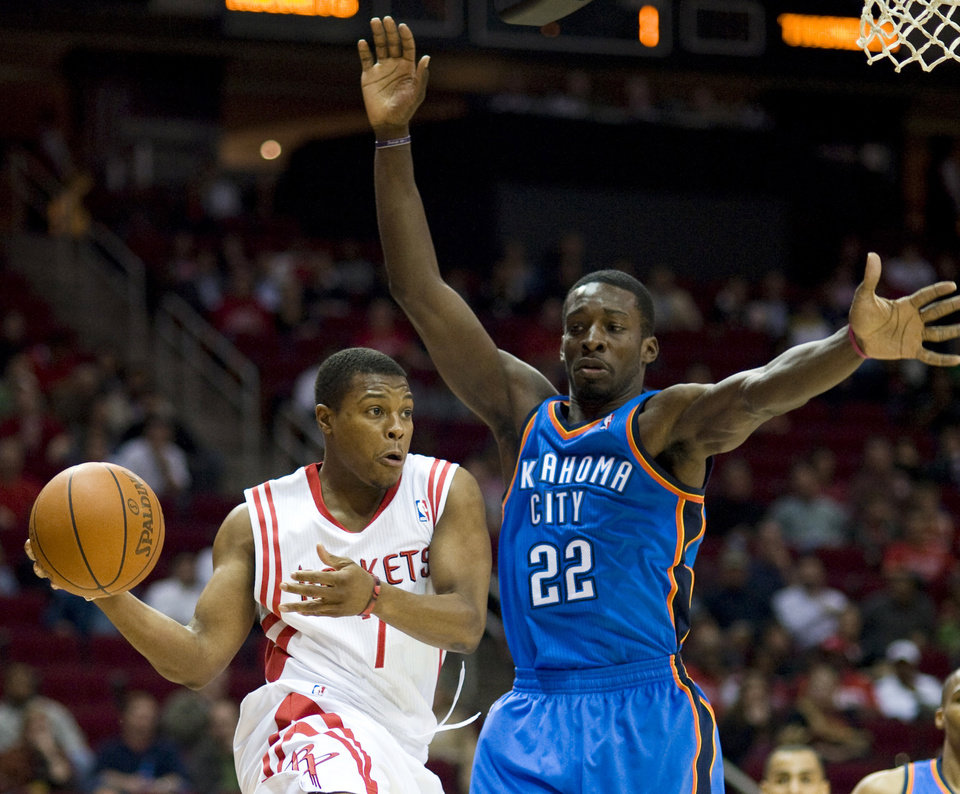 Photo - Houston's Kyle Lowry looks to pass while guarded by Thunder forward Jeff Green during Sunday's game. AP PHOTO